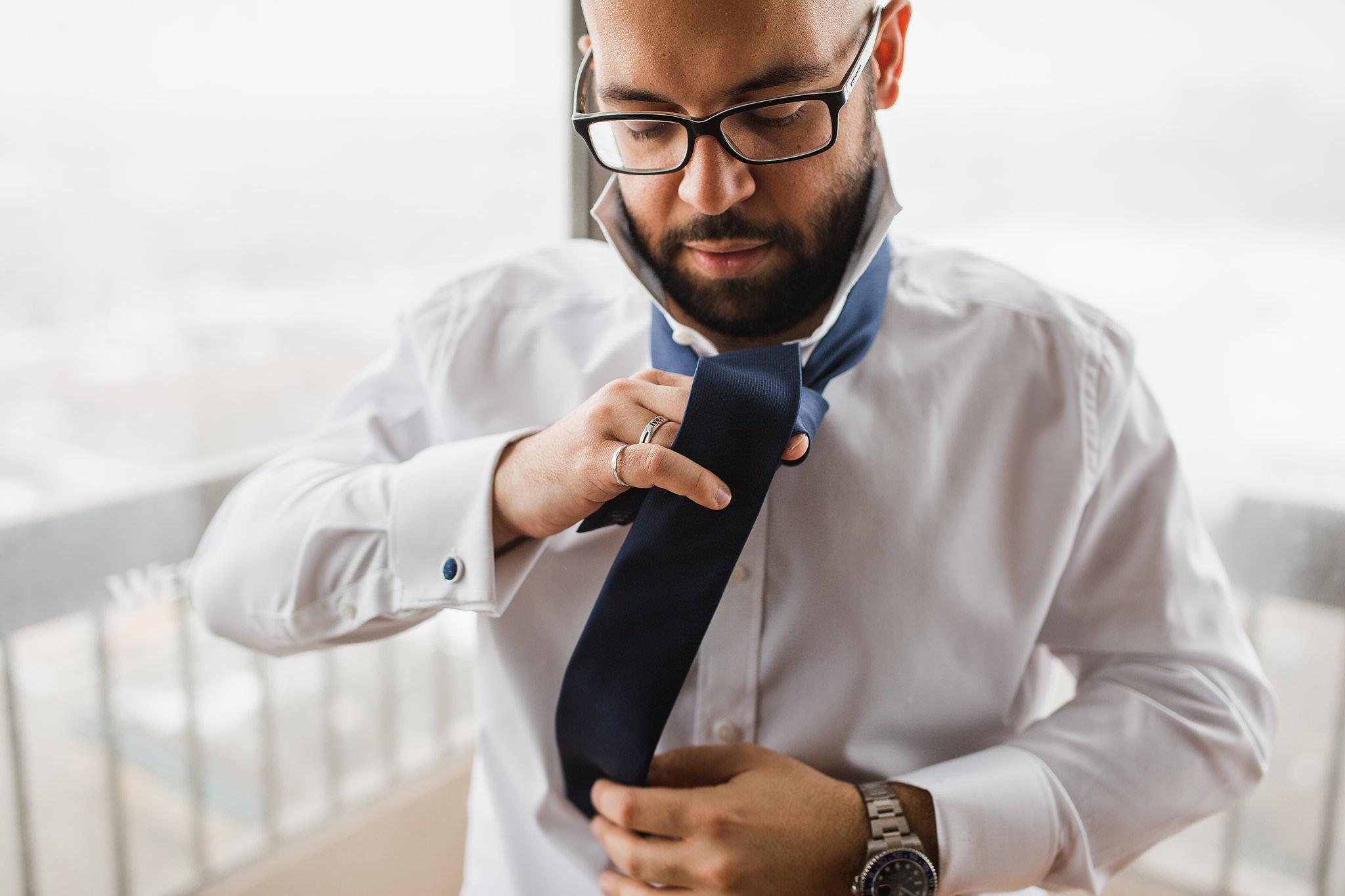 groom tying his tie infront of window