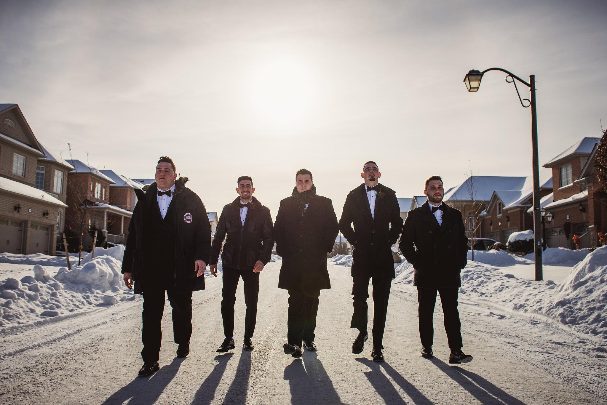 grooms and groomsmen walking down the street
