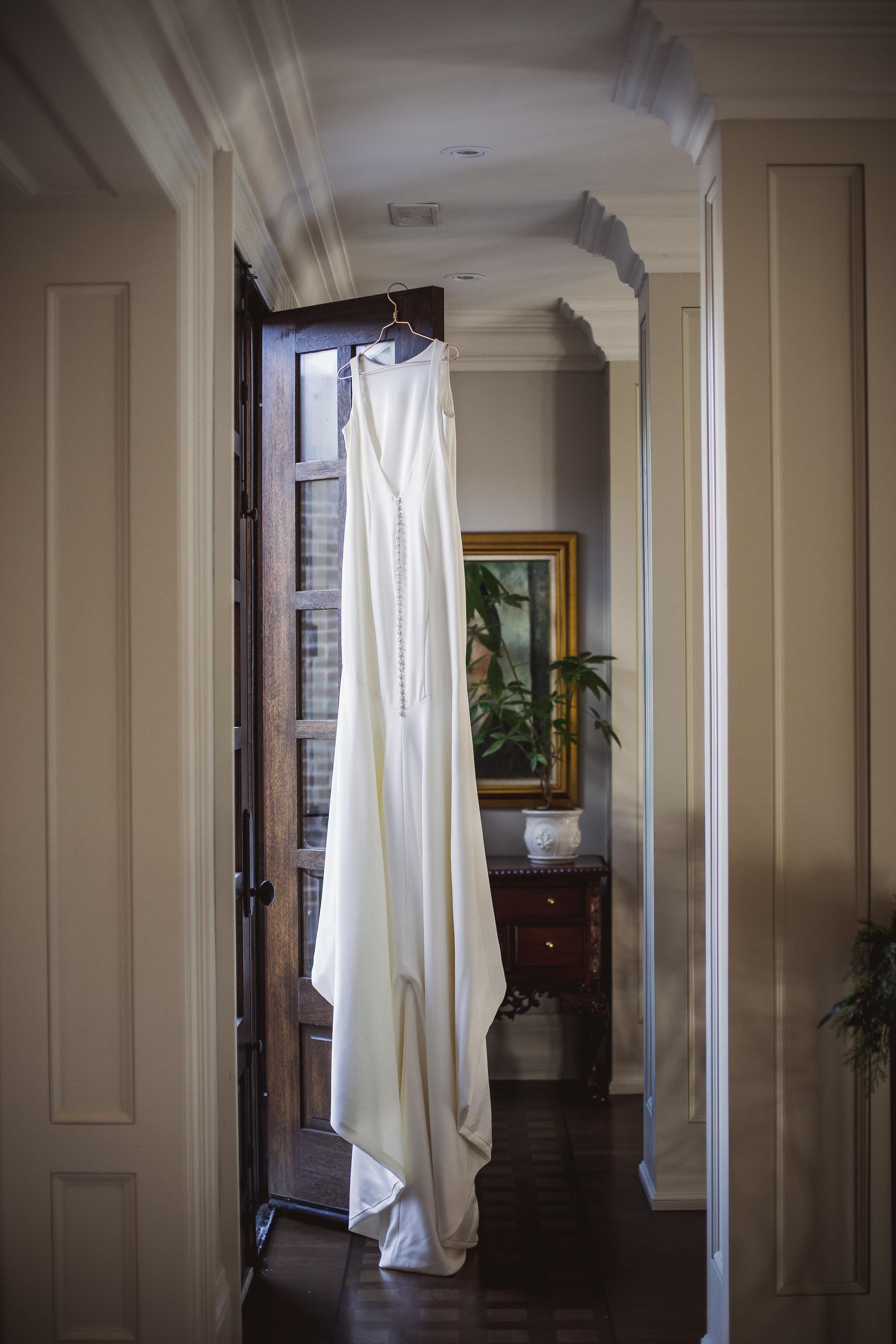 brides dress hanging in doorway