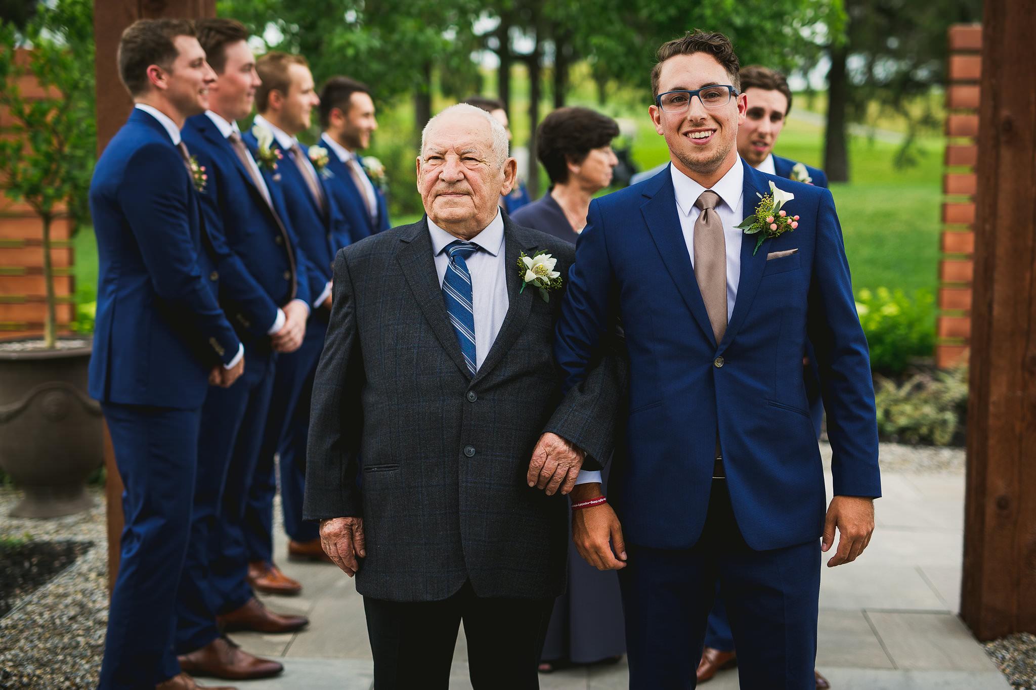 groomsman and grandpa walking down the aisle
