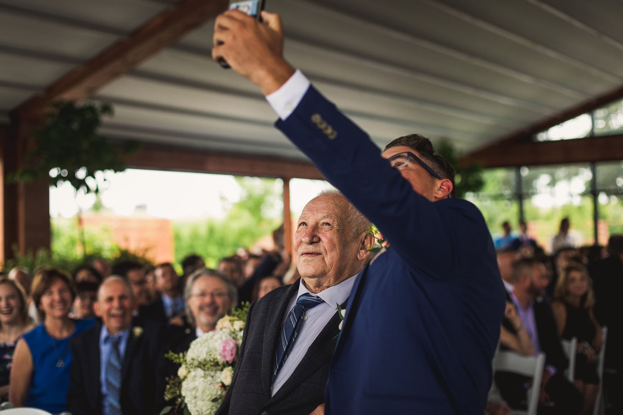 groomsman takes a selfie with grandpa while walking down the aisle