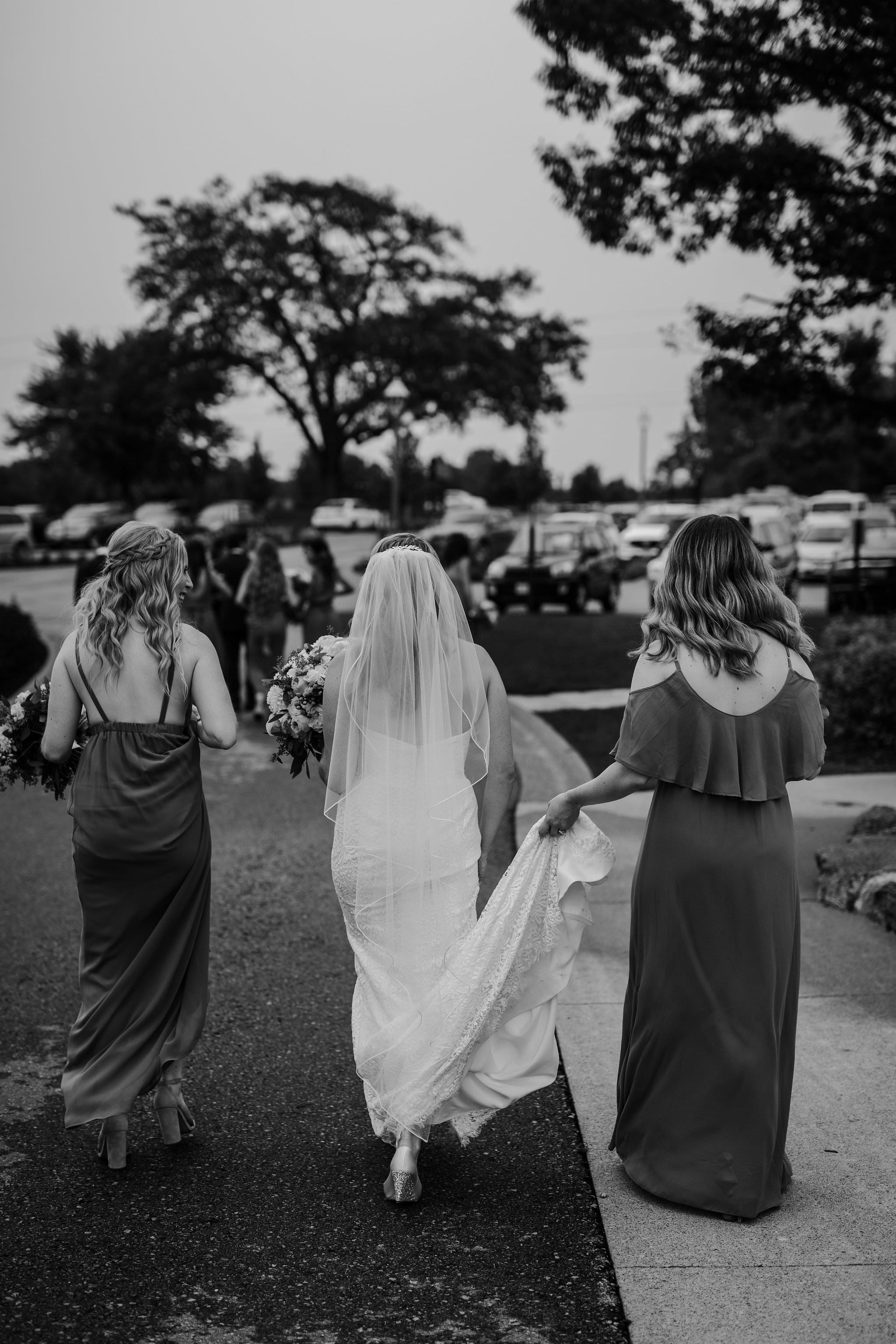 brides and bridesmaids walking away carrying train