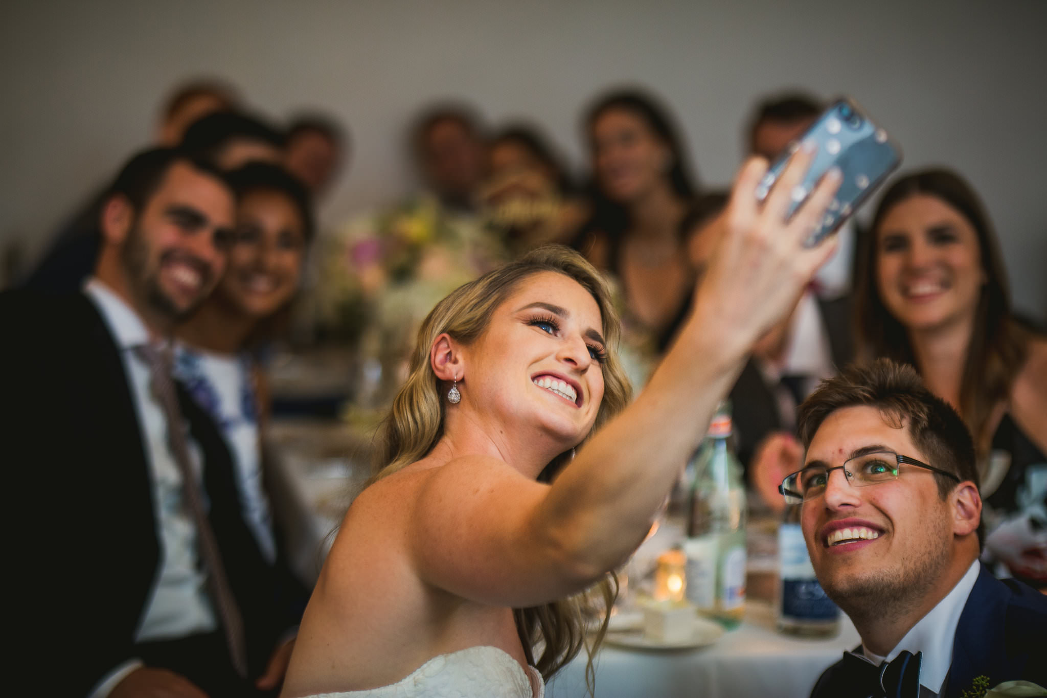 bride taking selfie with guests