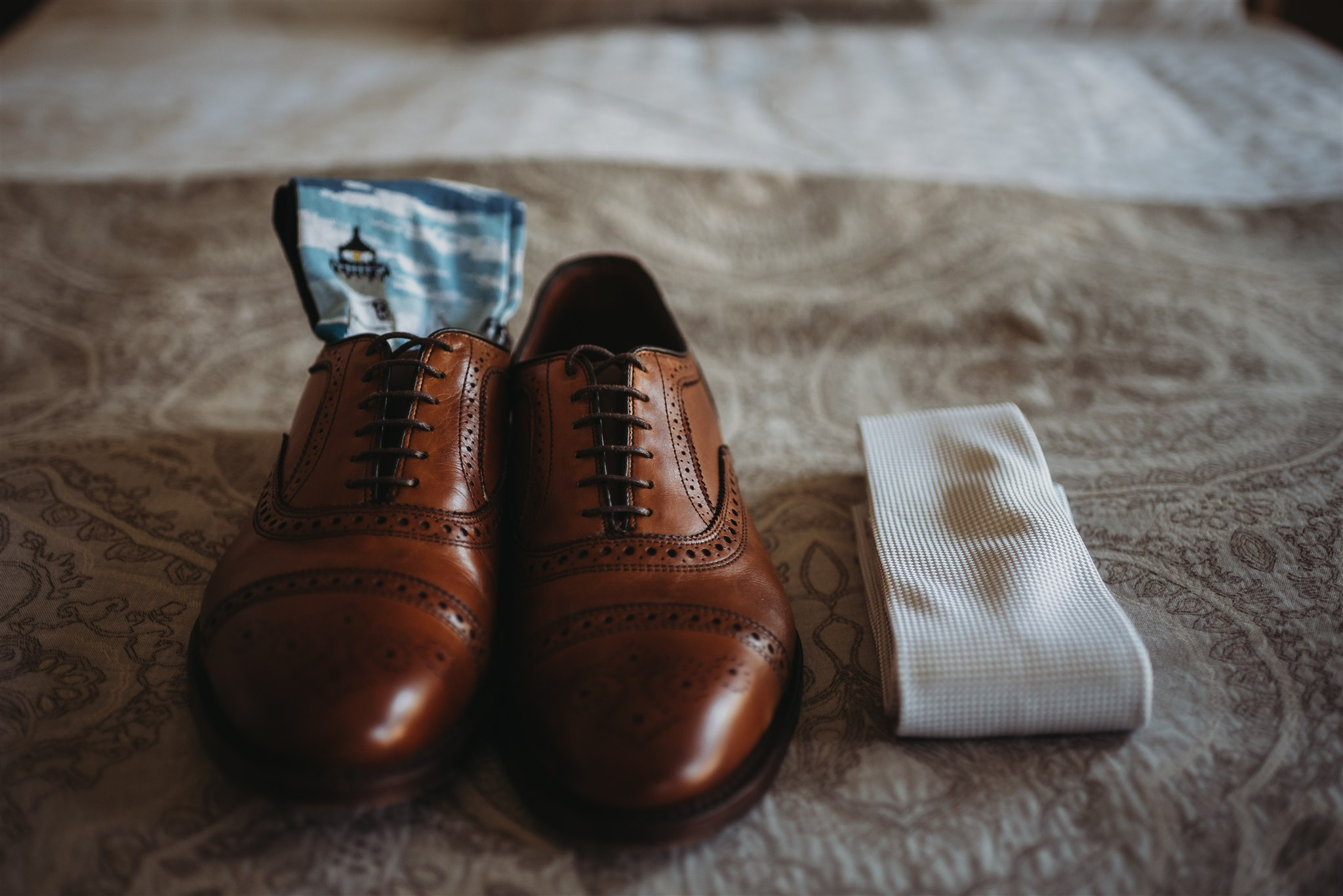 the grooms accessories photographed on the bed