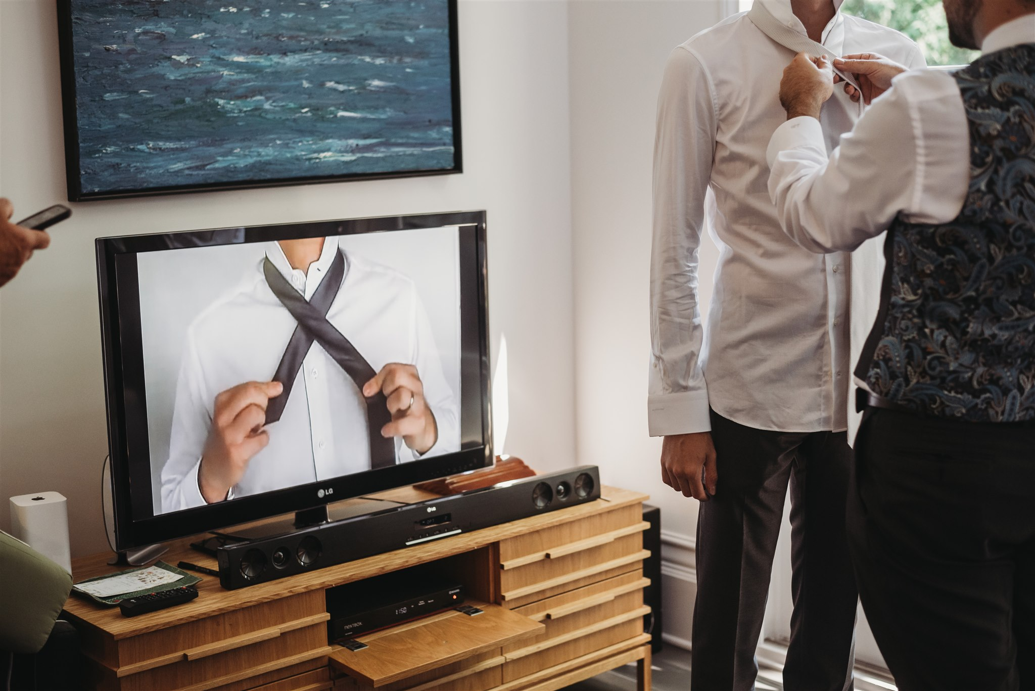 groom and groomsmen watching a youtube video on how to tie a tie