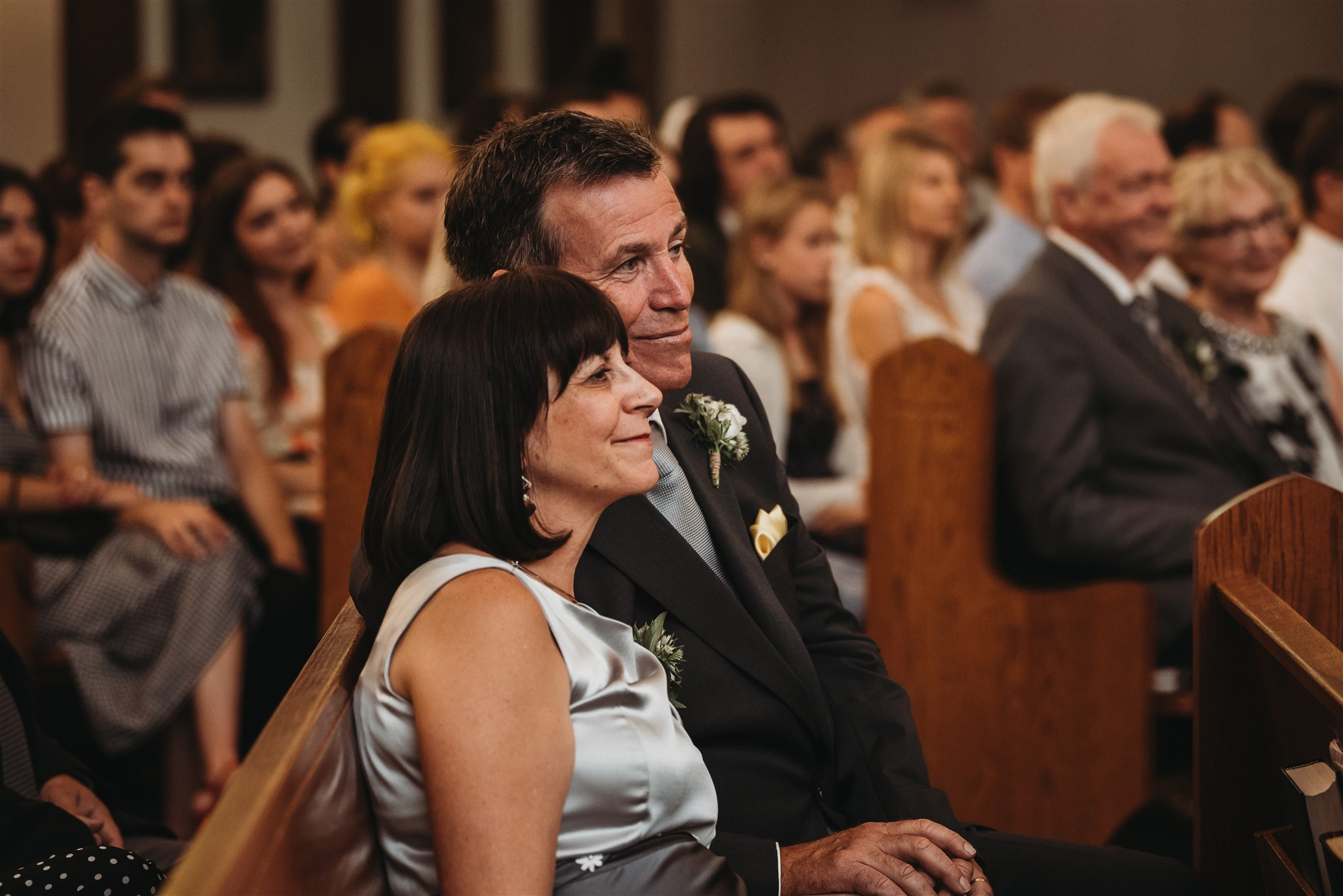 grooms parents looking at them with love during a formal catholic wedding ceremony