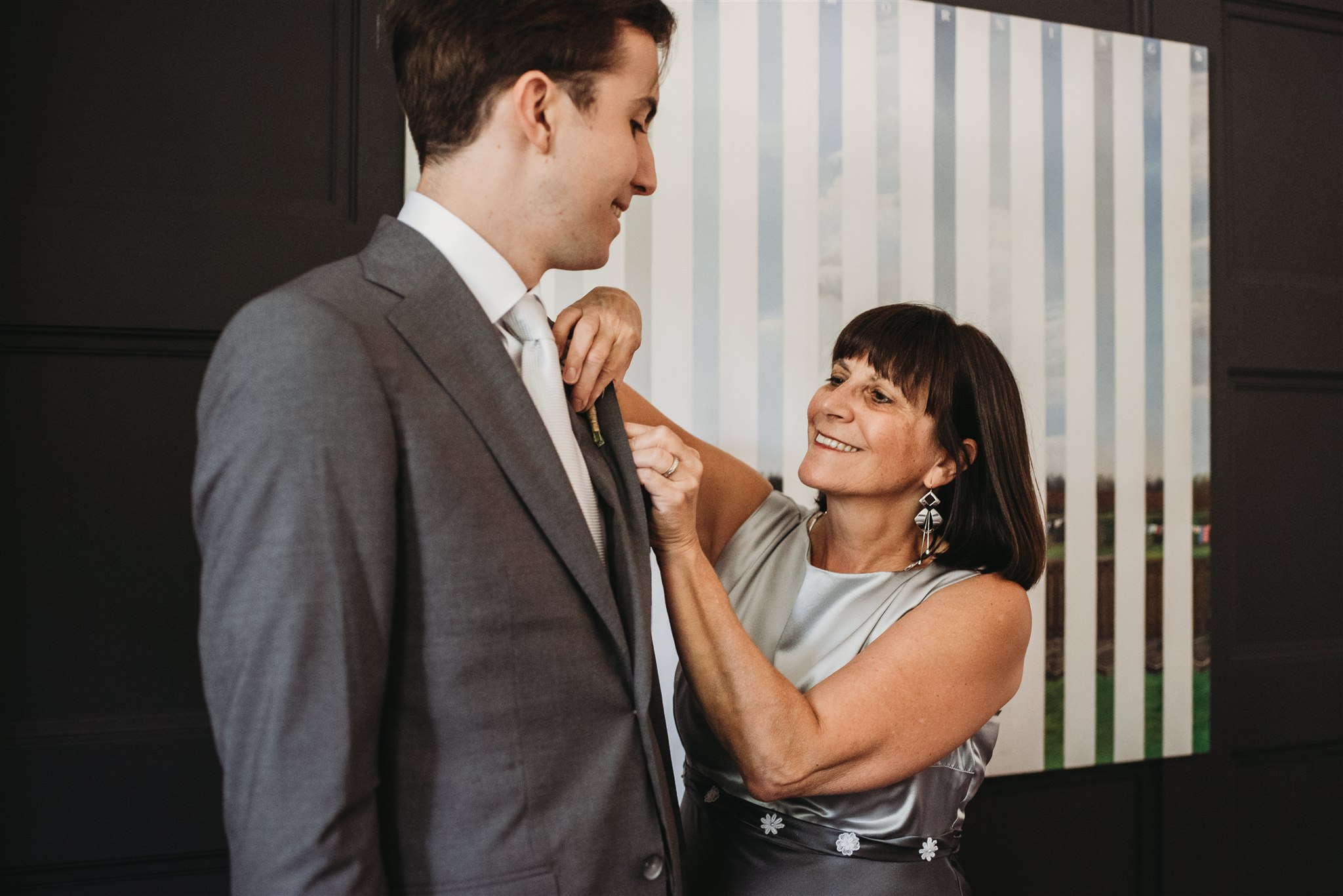 grooms mom putting his boutonniere on