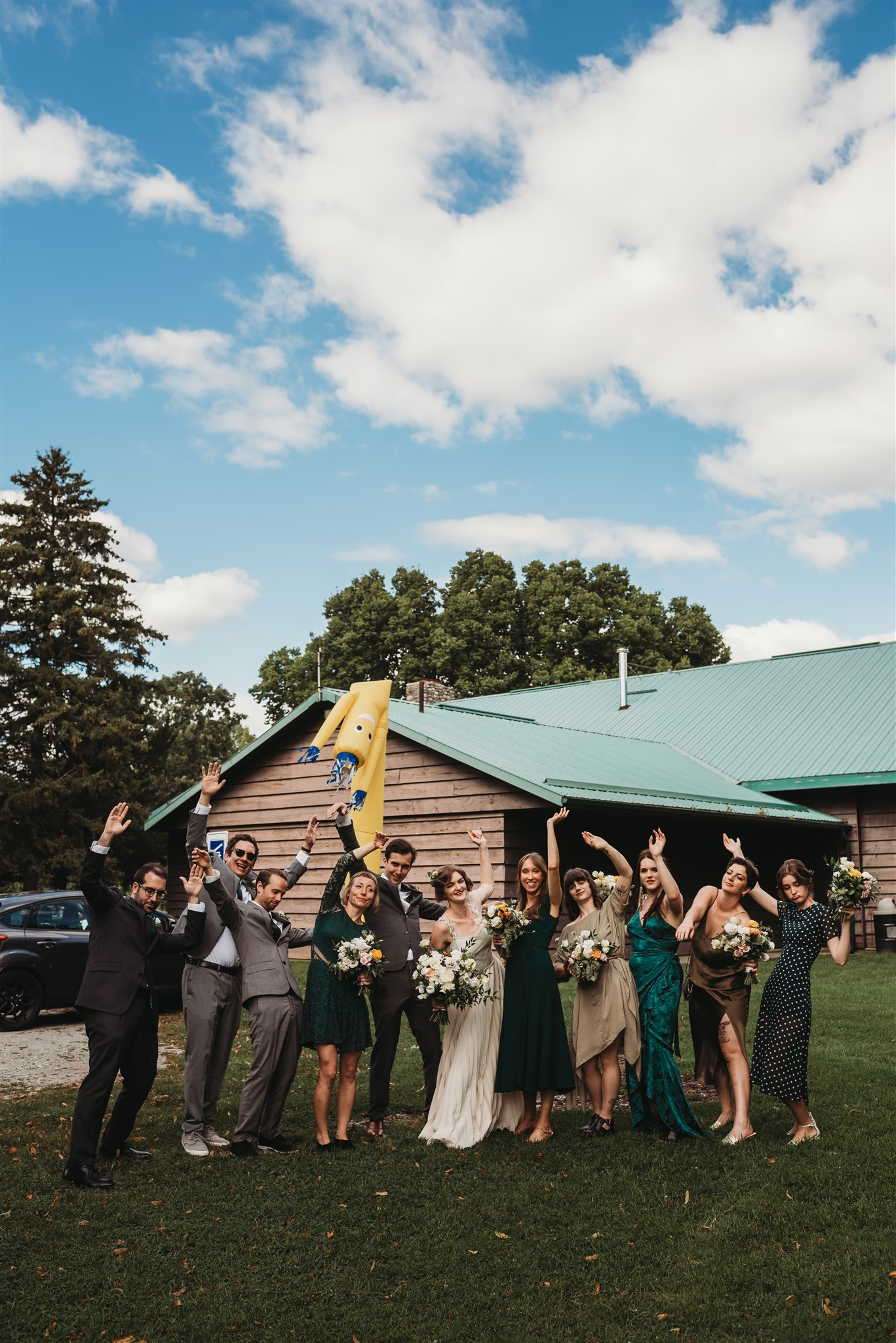 wedding party posing in front of wacky waving inflatable arm flailing tube man