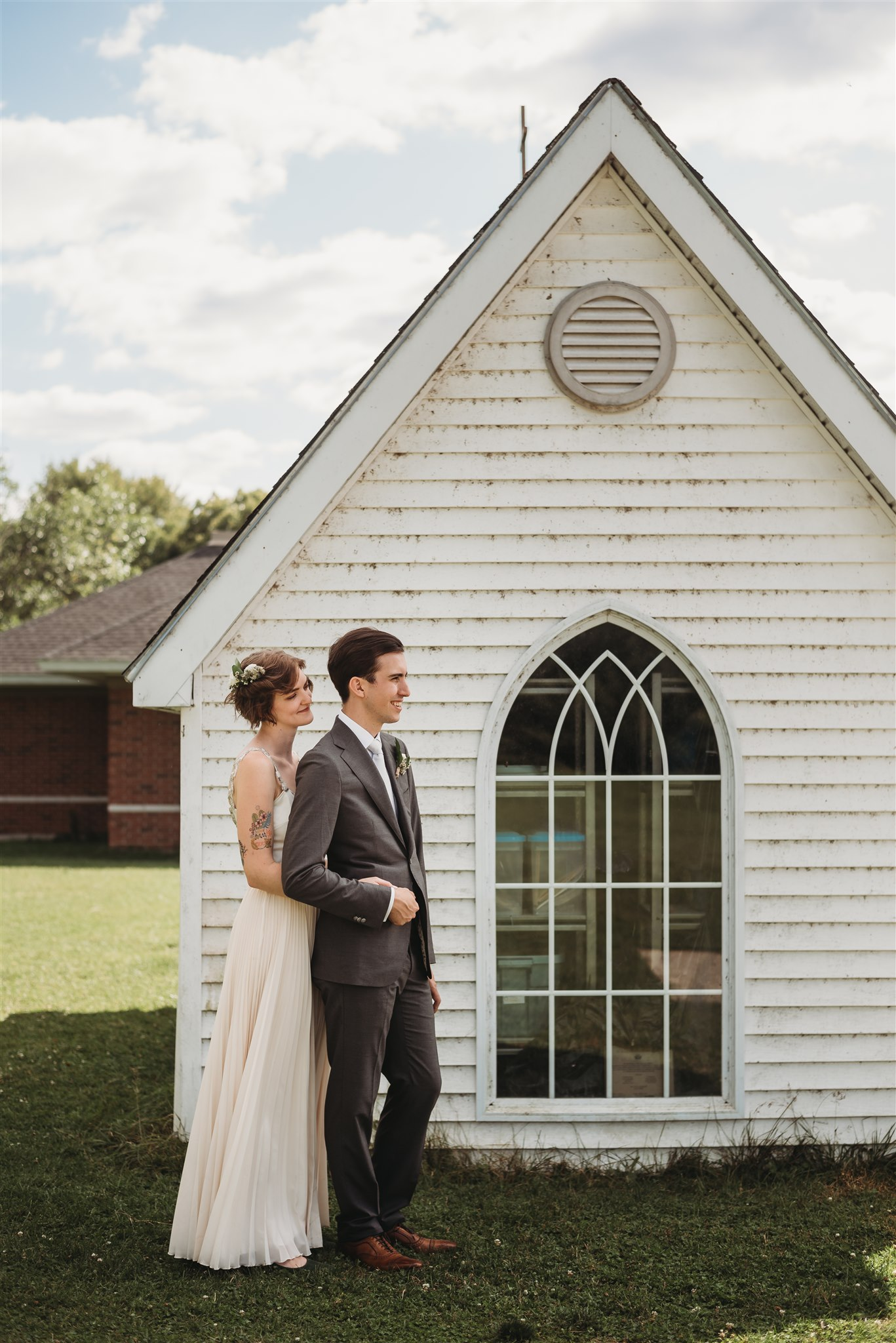 couple posing next to little church building