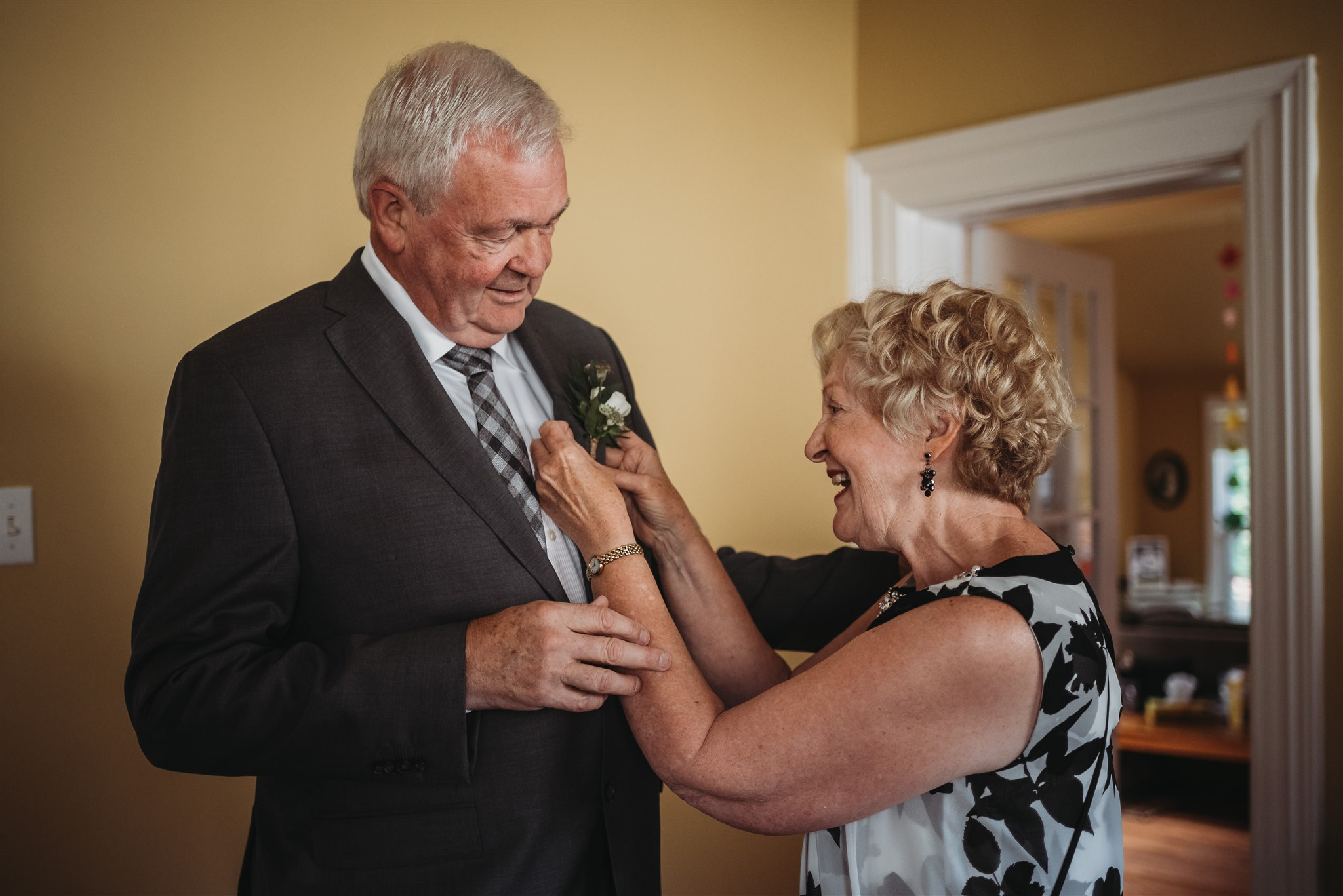 brides mom and dad putting boutonniere on