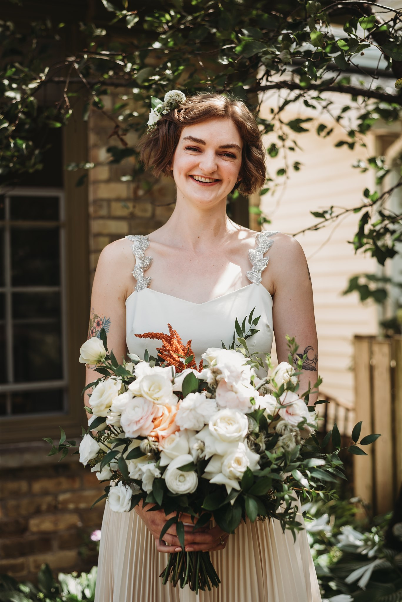 modern tattooed bride smiling with her bouquet