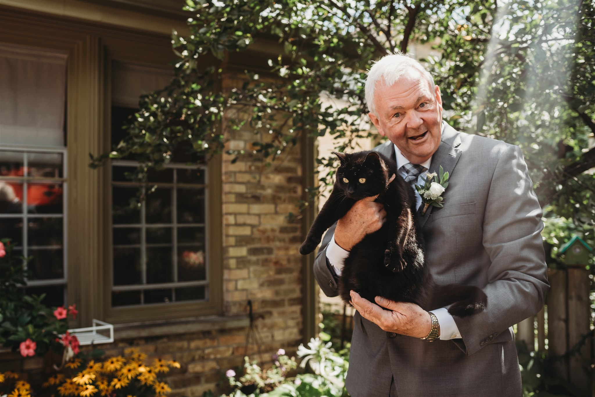 black cat on wedding day being held by brides dad