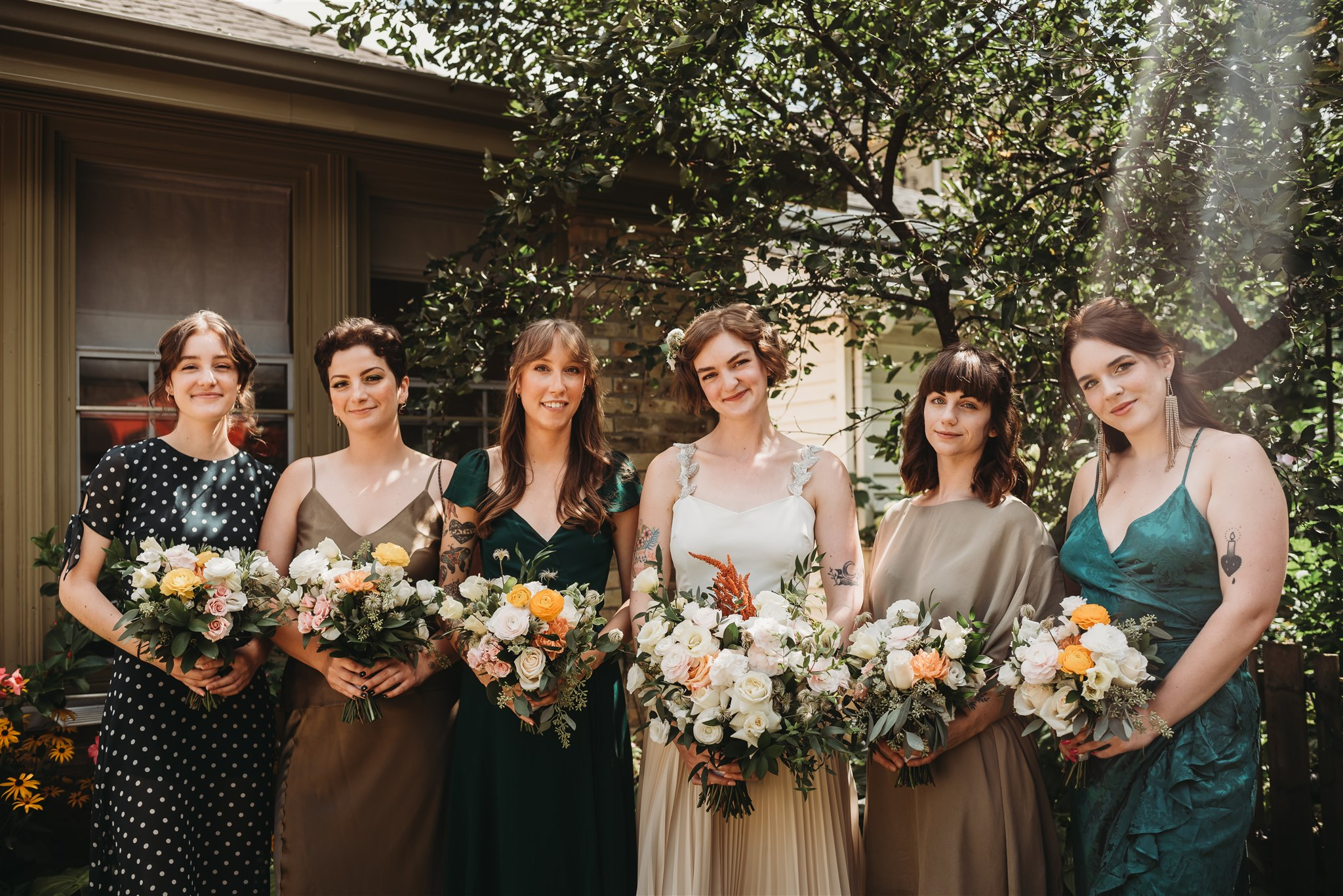 wedding party picture in backyard garden with mismatched dresses