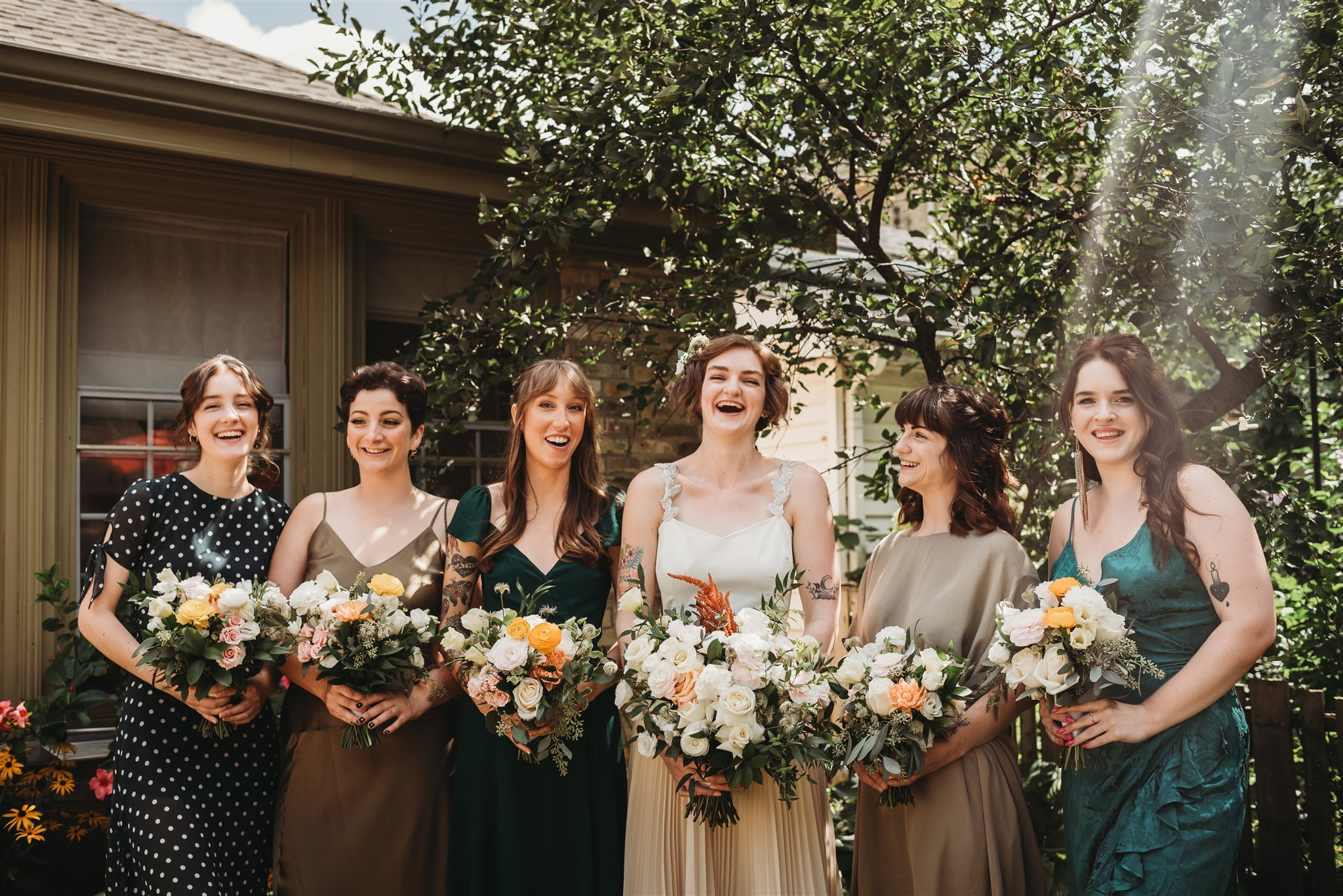 wedding party picture with bride and bridesmaids laughing in backyard garden with mismatched dresses