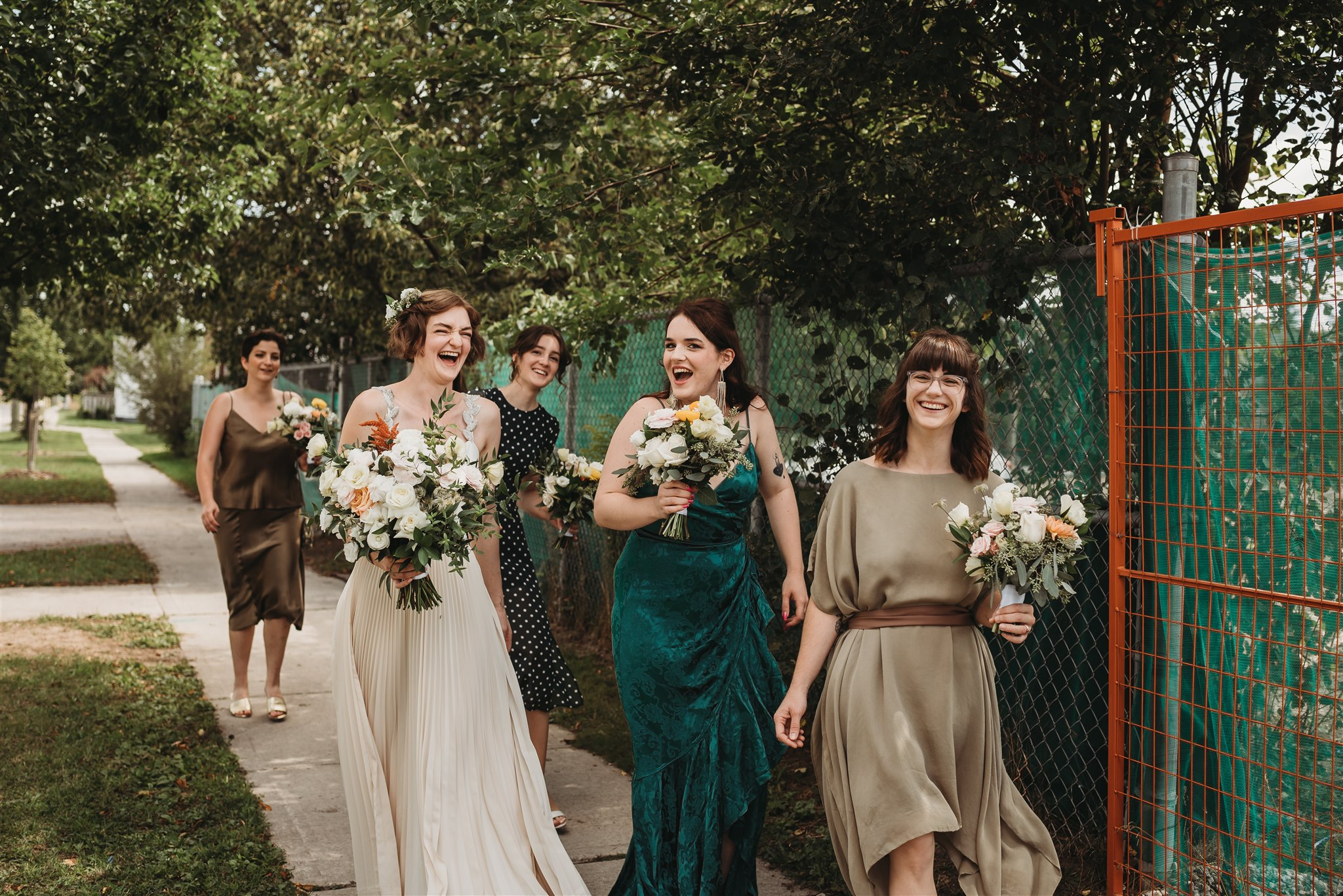 bride walking to ceremony with bridesmaids in green dresses